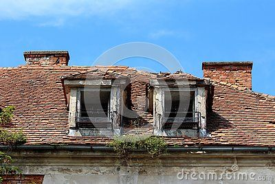 Two Destroyed Roof Windows With Rusted Metal Flower Holders On Abandoned Old Building With Broken And Missing Roof Tile Roof Window Metal Flowers Old Buildings