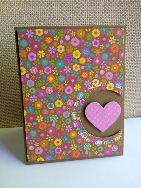 """Brilliant colors on the patterned flower paper just jump off the page on this handmade valentine's card. The """"Love You"""" stamps in white ink border the cut out circle with a plaid, pink, pastel heart."""
