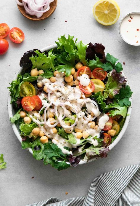 Easy green salad with protein rich chickpeas and creamy lemon tahini dressing is one of my favorite vegan salads to throw together in a pinch! #vegansalad #veganrecipes #healthyrecipes #veganrecipe #plantbased