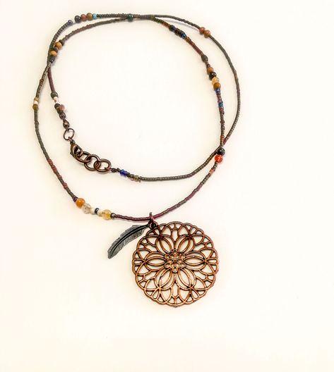 Collar hecho con cuentas y piedras y colgante con detalle de flor en cobre