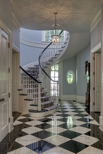 black and white marble floors. The sweep of the staircase up from checkerboard floor  black doors in fore and background glass door knobs even Wow