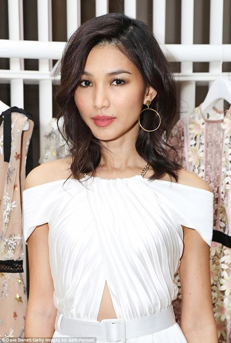 A vision in white:Turning heads, the Oxford graduate, 35, looked sensational in a pleated cream jumpsuit with off the shoulder detailing and a gold halter neck chain