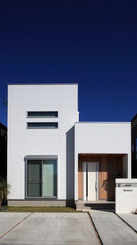 キューブ型のシンプルな外観 玄関まわりをレッドシダーの板貼りにし