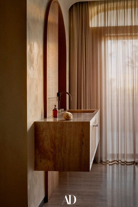 In the primary bathroom, the sink and cabinet in travertine and oak were custom made by Caprini  Pellerin Architectes. #bathrooms #bathroomideas #primarybathrooms #sink #cabinets #wood #neutrals #earthtones #oak #curtains #design #minimalist