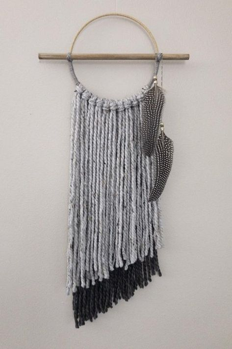 Add a unique piece to your boho chic wall decor with this modern asymmetrical dreamcatcher-inspired yarn tapestry. This bohemian style wall hanging was handcrafted with chunky gray and charcoal yarn, a gray-washed wooden dowel, a metal hoop wrapped in grey twine below and beige with gold twine above, and finished off with a silver-tone necklace chain that holds feathers adorned with beads.