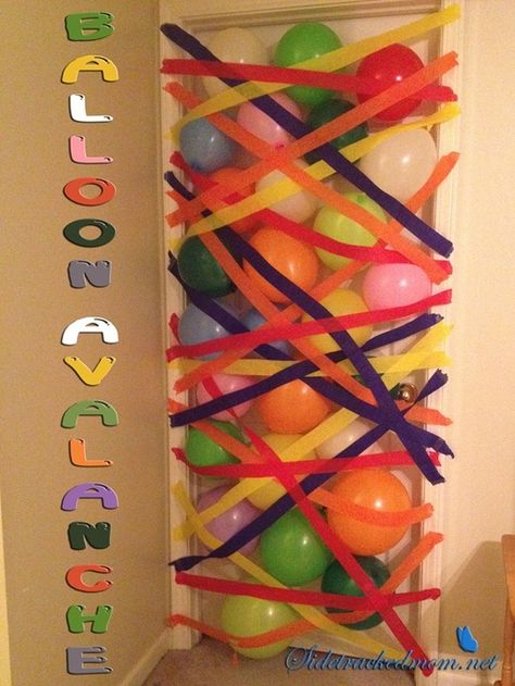 Birthday kid gets a ballon avalanche when he/she opens the door in the AM.  Pinned this before but this one uses crepe paper to hold the balloons instead of a sheet of plastic, which is way better, because then they get to rip through the paper!