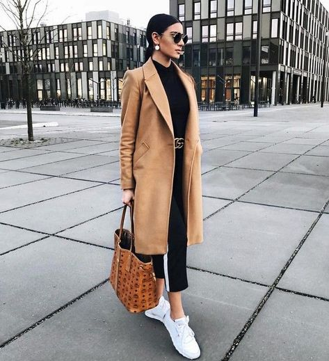 Classic camel coat over all black casual outfit with chic black leather belt. Classic camel coat over all black casual outfit with chic black leather belt.