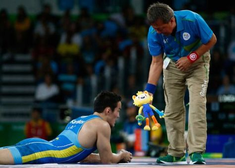 Doszhan Kartikov of Kazakhstan is shown an Olympic mascot doll by a coach during competition against Elvin Mursaliyev of Azerbaijan during the Men's 59 kg Greco-Roman Wrestling 1/8 Final on Day 9 of the Rio 2016 Olympic Games at the Carioca Arena 2 on August 15, 2016 in Rio de Janeiro, Brazil.