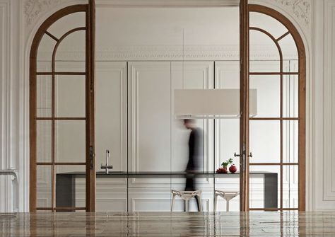 INVISIBLE KITCHEN,  i29 designed a Paris kitchen that acts more as a piece of furniture instead of as a kitchen.  Large sliding wall panels with moldings conceal all kitchen appliances and storage space.