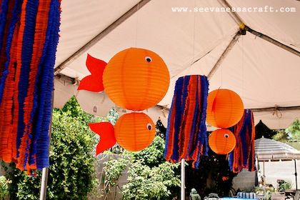 under the sea party ideas - orange paper lanterns and transformed them into cute little fish by simply adding a tail and googly eyes! Love! The streamers are great too! They give the feel of an underwater adventure!