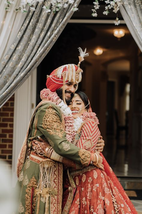 Sikh bride and groom embrace after placing the mala's on each toher. Photograph by Catch Motion Photography, VA #happycouple #sikhbrideandgroom #indianwedding #virginiaphotography #wedding #varmalaintroduction #covidwedding