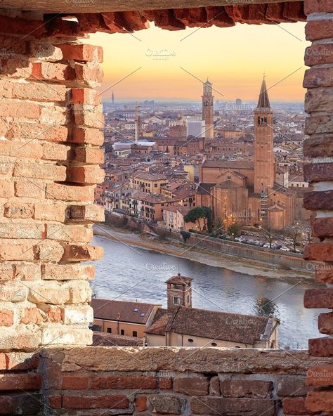 Old Verona town, view through brickwall window Photos Verona historical quarter from viewpoint at sunset, Italy by sweet spot