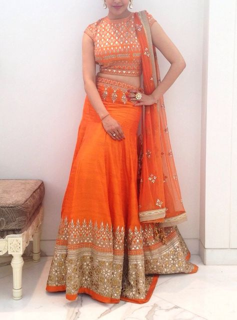 This exquisite orange lehenga choli is adorned with traditional gotta patti embroidery. This lehenga choli has been paired with a fully embroidered ornage raw silk choli and a net dupatta. A stunning