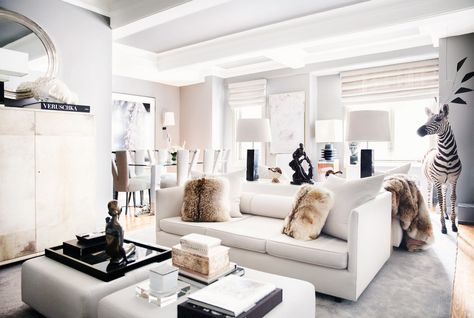 Neutral and warm living room with faux fur pillows and black art