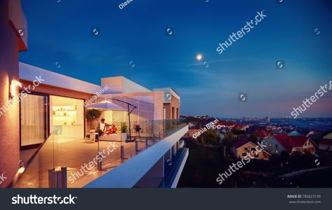 Family Relaxing On Roof Top Patio With Evening City Viewroof Top