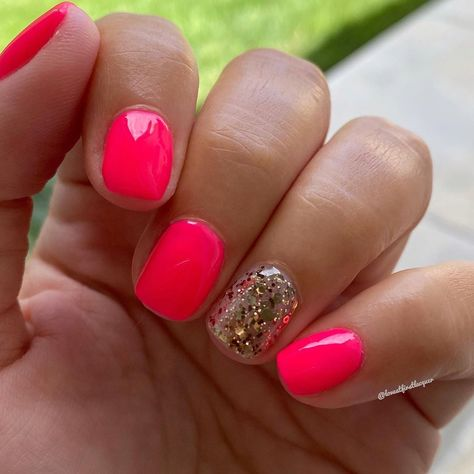 Bright neon pink nails for summer. Shirt nails with a hot pink and gold glitter accent nail.