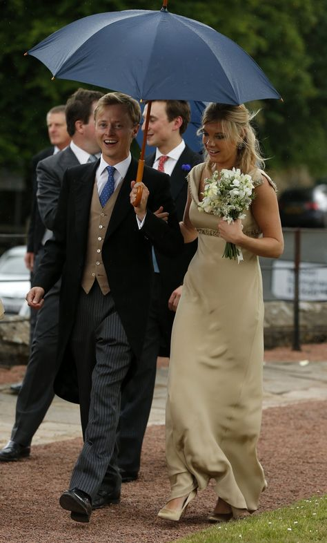 Bridesmaid Chelsey Davy shelters under an umbrella as she leaves the wedding