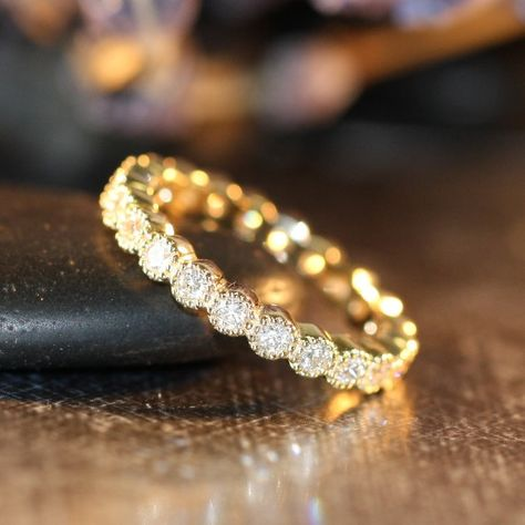 This vintage inspired eternity band features a full circle of round brilliant cut conflict free diamonds set in a solid 14k yellow gold bezel