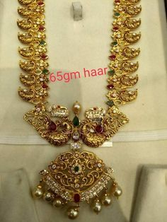 Stunning gold long necklace with dancing peacock desig. Necklace having mango hangings. Mango s with peacock design. Necklace studded with precious stones.
