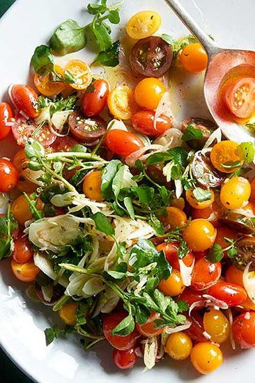 This tomato salad is one of our favorite Memorial Day barbecue recipes because it's so easy! Toss tiny tomatoes with arugula, fennel, and parsley for a quick and easy side dish. #memorialdayideas #memorialdayparty #sidedishideas #partysidedish #bhg