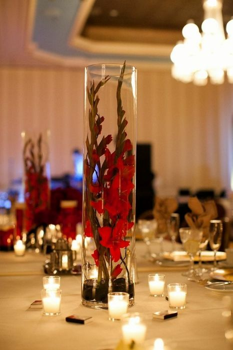 Place 2 stems of the same color gladiola stems in a tall cylinder vase to create a dramatic and budget friendly centerpiece for a wedding or other special event.  Be sure to give the gladiolas time to open. #wedding #gladiola redcenterpiece