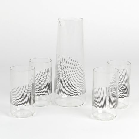 A carafe and set of tumblers printed with fine black lines that overlap to create a moiré effect when the pieces are clustered together