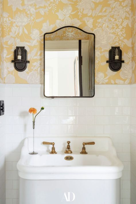 Buttercup yellow wallpaper makes for a particularly sunny powder room. #bathrooms #bathroomideas #bathroominspo #wallpaper #sink #tile #candles #design