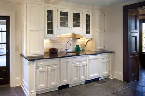 This large white kitchen even has room for a wet bar with an integrated ice maker and beverage center and a small bar sink and bar faucet.