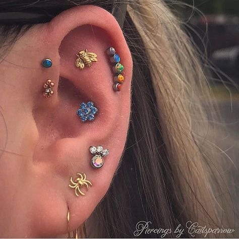 ✨Piercing today @irishjayhooligans 12-8!✨ Here's some progress made on @thatmetalchick  super colorful ear from yesterday! I got to pierce her flat with a 14k gold bee from @leroifinejewelry and a third lobe piercing with a little titanium cluster with three 1.5 cz's and a 4mm AB cz! Her helix, flat, and third lobe piercing were done be me, the rest were not, but most of them have been upgraded by this point. Thanks for always getting such fun piercings, I love how this is all coming together.