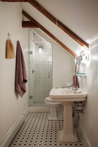Vintage-inspired tile on the floor and the shower walls,  beadboard walls up to the ceiling, and a salvaged pedestal sink lend period authenticity to this  under-the-eaves bath. | Photo: Eric Roth
