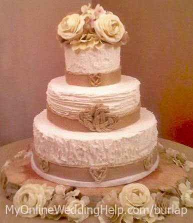 Rustic wedding idea: have a burlap-decorated rustic wedding cake (back the fabric with wax paper so it doesn't touch frosting). Roses and burlap topper and decor around the wooden tree base add a bit of vintage romance. Icing is buttercream decorated like tree bark (middle is ruffle-ish design). #MyOnlineWeddingHelp