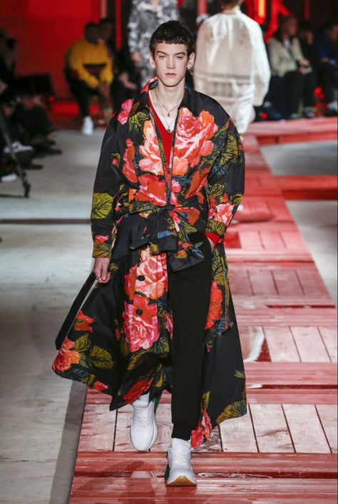 Vogue, C. 2018. Alexander McQueen's Fall/Winter collection displays Avant Garde in the photo by having large floral prints all over the outfit. It also shows by the jacket draping on the body and the different dimensions of the fabric and floral print as the model walks down the runway.
