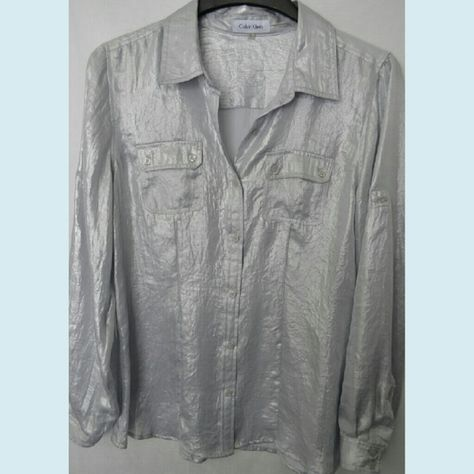"CALVIN KLEIN Silver Lame Blouse Silvrr lame button down blouse. Size M. Silver lame has slight shimmer. Two frontal flap button pockets. Roll up button tie for sleeves. 100% Poly. Bust 32""-34"". Great to wear for girl's night out!???? Like new condition. Accessories shown are sold separately. Calvin Klein Tops Button Down Shirts"