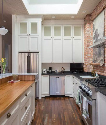 White Kitchen With High Ceilings Skylight And Exposed Brick Wall Home Brick Kitchen Kitchen With High Ceilings
