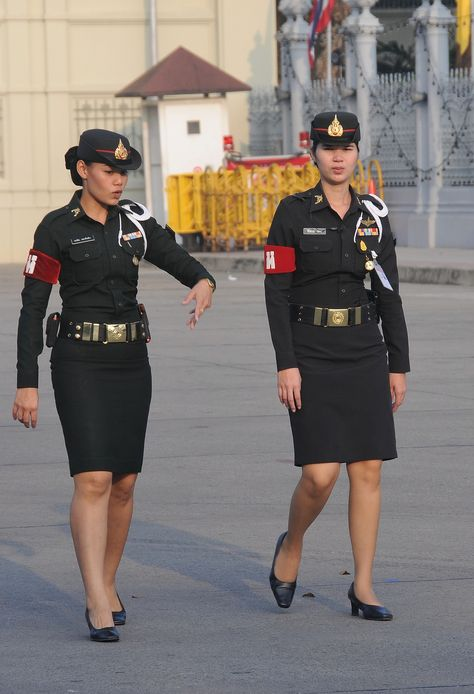 "Thai military policewomen make an arrest. ""Don't move!"" one calls out. ""Turn round and place your hands behind your back!"""