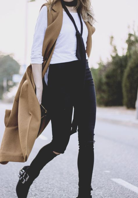 Isabel Sellés is wearing the skinny scarf trend in a sleek and stylish manner, combining a sleeveless camel maxi coat and a plain white blouse with a black tie style scarf. We love this chic...