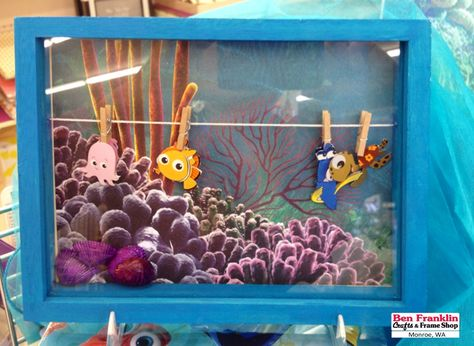 DIY SEA LIFE FRAMED ART -  This unfinished frame comes with the string and mini clothespins already put together. Paint the frame, glue paper for sea background effect, hang layered stickers with clothespins. | Supplies available at our Ben Franklin Crafts store in Monroe, WA.   @EKSuccess #FindingNemo #FindingDory