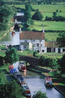 By boat, travel narrow English canals built in the late 18th century.  http://canalrivertrust.org.uk/