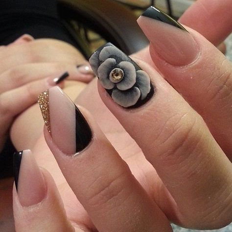 A very seductive looking nail art design in striking black, gray and gold details, with gold dust and a huge gray flower detail adorned with a gold bead.