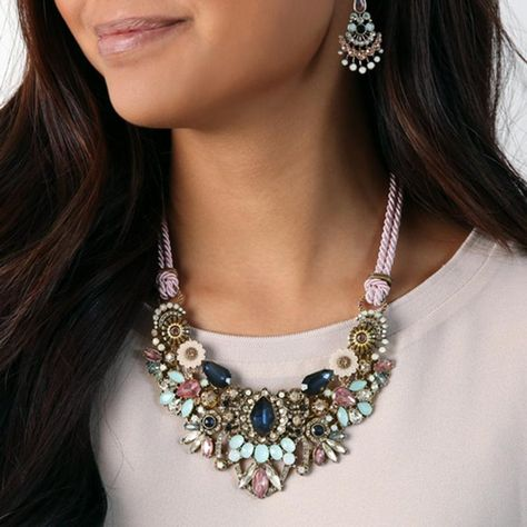 """NECKLACE: Feminine florals + bursts of crystals take center-stage in this romantic statement piece. A sweet pink cord can be swapped out for an antique gold chain for an edgy feel. Either way, this wow-worthy style is not to be missed on your journey through Spring. light amethyst, peach + white opal crystal, vintage pink, tonal blue-green + frosted ivory resin, light pink rope antique gold-plated 18"""" approx. length + 2"""" extender lobster clasp rope + chain back option BRACELET: SOLD OUT JEW-0063"""