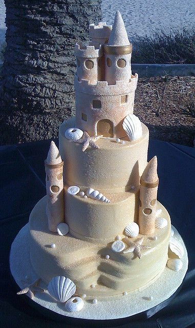 Sand Castle Cake --- The winner of beach theme wedding cakes, as far as I'm concerned. I hope the seashells are molded white chocolate. Add blended graham cracker for sand