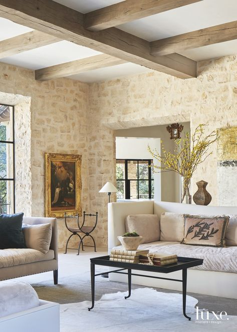 Hand-chiseled stone, wrought iron and antique wood introduce a deep sense of history into this elegant Austin home by designer Marcus Mohon.