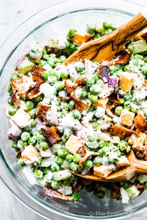 PIN TO SAVE FOR LATER! This creamy pea salad with bacon is a classic side dish and a great way to use a bag of frozen peas. The peas are mixed with some cheddar cheese cubes, crunchy celery, red onion, and a yogurt-based creamy dressing. A little bacon at the end makes this taste like a real treat. #theendlessmeal #peasalad #peas #pearecipes #greenpeas #greenpearecipes #salad #saladrecipes #spring #springrecipes #bacon #sidedish #picnicrecipes #potluckrecipes #summerrecipes