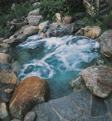 an outdoor hot tub fully clad with rocks and stones looks all natural and relaxes you even more thanks to that