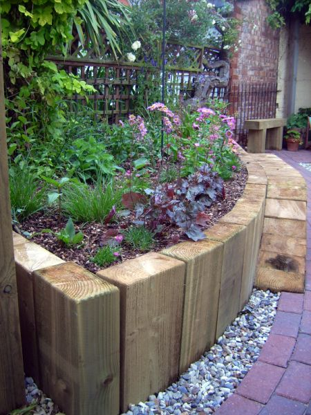 use vertical railway sleepers to create a curved wall raised beds - curved walls may work with overall design better divide between Mediterranean garden and English garden rather than original oblong med wall bed idea