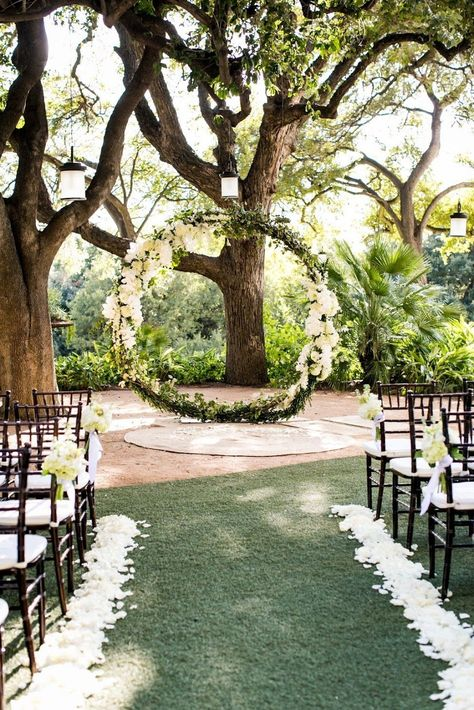 Outdoor wedding ceremony with gorgeous floral arrangement at the alter along with white rose petals lining the aisle | For more information on the Four Seasons Hotel and other wedding venues, visit myweddingscout.com | Four Seasons Hotel | Cory Ryan #weddingceremony #outdoorwedding #hotelwedding #weddingflorals #weddingvenue #austinweddingvenue