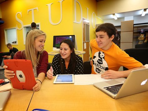 A teaching candidate helps students use technology to complete an assignment.