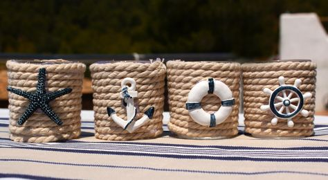 portavelas de vidrio forrados con cuerda y adornos marineros.