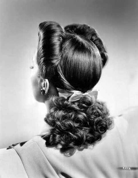 nancy kelly's hair is parted in the middle, brought up from the sides in fan-shaped puffs, + the crown is shaped into the head with twisted strands of hair brought from the sides + caught at the back with a gold metallic bow   1940   #vintage #1940s #hair