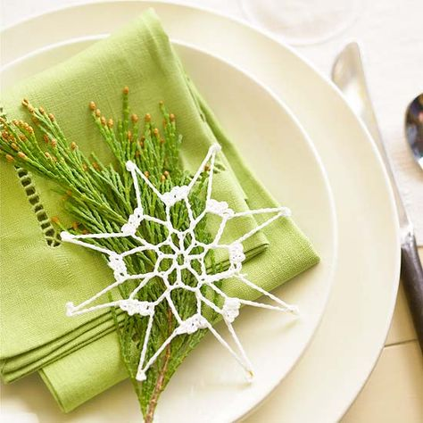 Who needs napkin rings? Set a simple crocheted star ornament atop a fragrant evergreen sprig at each place setting! http://www.bhg.com/christmas/indoor-decorating/festive-holiday-napkin-ideas/?socsrc=bhgpin121914starornamentplacesetting&page=17
